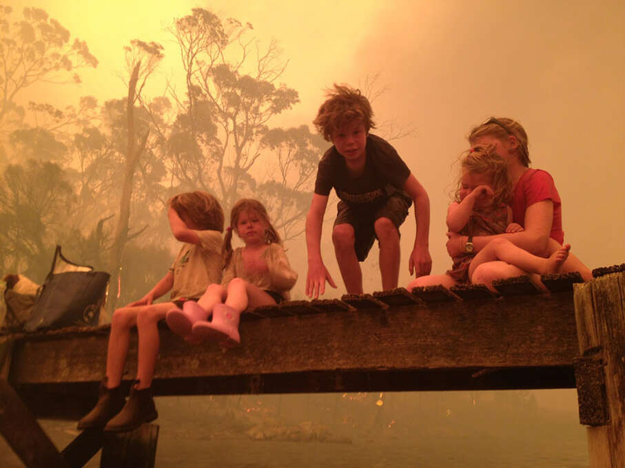 The Holmes family, the Walker siblings six-year-old Caleb, left, four-year-old Esther, second from left, nine-year-old Liam, and eleven-year-old Matilda, right, holding two-year-old Charlotte, prepare to enter the water on Jan. 4 to take refuge with their grandparents under a jetty as a wildfire rages nearby in the Tasmanian town of Dunalley, east of the state capital of Hobart, Australia. The family credits God with their survival from the fire that destroyed around 90 homes in Dunalley. Record temperatures across southern Australia cooled Wednesday reducing the danger from scores of raging wildfires but likely bringing only a brief reprieve from the summer�s extreme heat and fire risk. (AP Photo/The Holms Family, Tim Holmes) Photo: AP