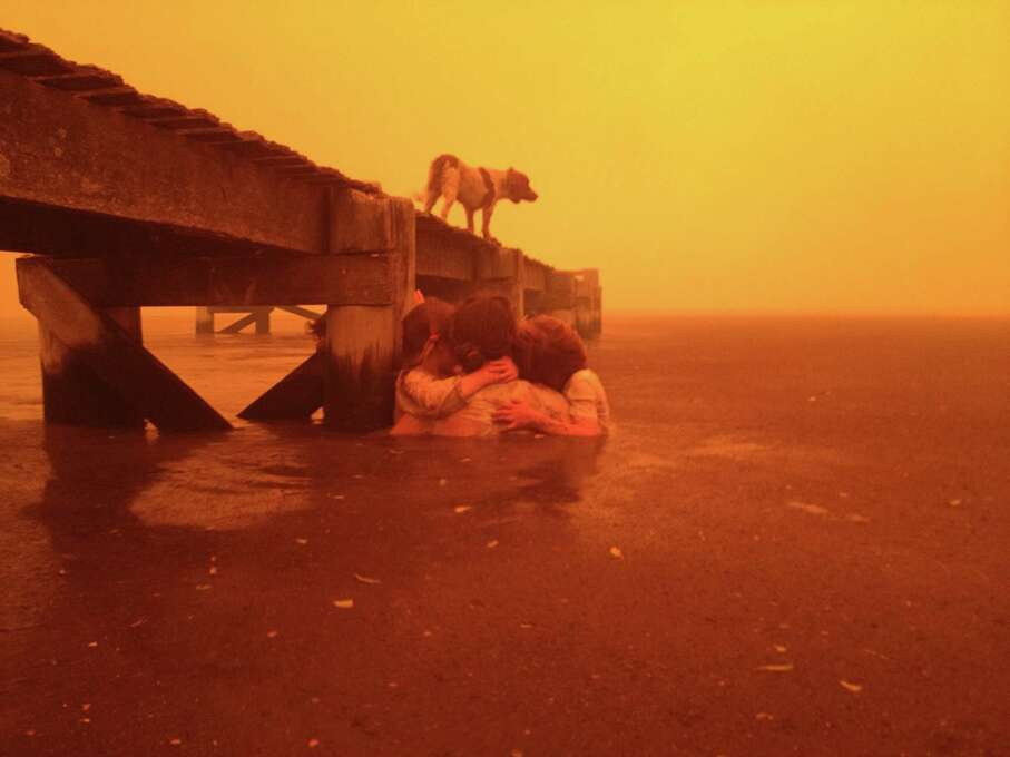 The Holmes family,  Tammy Holmes and her grandchildren take refuge under a jetty on Jan. 4 as a wildfire rages nearby in the Tasmanian town of Dunalley, east of the state capital of Hobart, Australia. The family credits God with their survival from the fire that destroyed around 90 homes in Dunalley. Record temperatures across southern Australia cooled Wednesday, Jan. 9, 2013, reducing the danger from scores of raging wildfires but likely bringing only a brief reprieve from the summer�s extreme heat and fire risk. (AP Photo/Holmes Family, Tim Holmes) Photo: AP