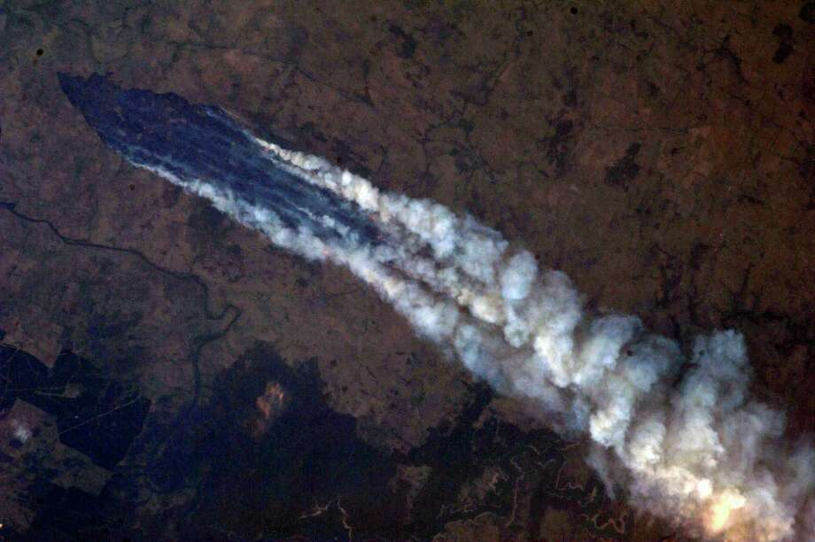 RE-TRANS FOR HIGHER RESOLUTION - This Tuesday Jan. 8, 2013 photo provided by NASA, taken by Astronaut Chris Hadfield from the International Space Station, shows a view of the wildfire near Burrinjuck Dam in Australia. Look closely and you can see the flames from orbit. Photo: AP