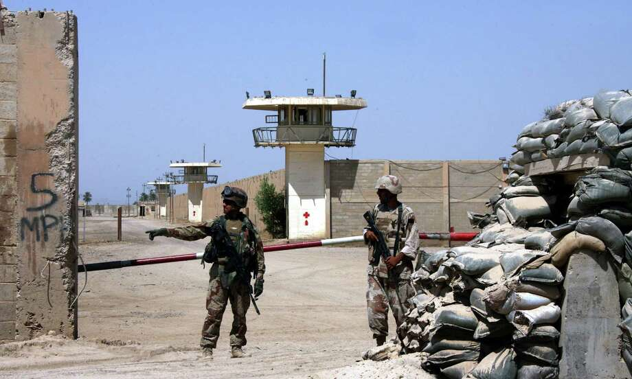 In this 2006, file photo, Iraqi army soldiers stand guard at the Abu Ghraib prison, after taking over from U.S. soldiers, on the outskirts of Baghdad, Iraq. A defense contractor whose subsidiary was accused in a lawsuit of conspiring to engage in torture at the infamous Abu Ghraib prison in Iraq has paid $5.28 million to 71 former inmates held there and at other U.S.-run detention facilities between 2003 and 2007. The settlement in the case involving Engility Holdings Inc. of Chantilly, Va., marks the first successful effort by lawyers for former prisoners at Abu Ghraib and other detention centers to collect money from a U.S. defense contractor in lawsuits alleging torture. Another contractor, CACI, is expected to go to trial over similar allegations this summer. Photo: AP