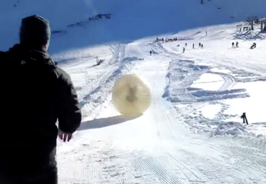 In this frame grab made Wednesday from APTN video provided by Yekaterina Achkasova, as her husband Denis Burakov and another man are seen inside a large plastic ball called a zorb, on Thursday as they roll down a hill beore tragedy struck at the winter sports venue at Dombai in the Caucasus Mountains of southern Russia.  What was supposed to be a thrilling ride down a ski slope inside a giant inflatable ball has ended in tragedy when the zorb veered off course and sailed over a cliff, killing Denis Burakov and leaving the other man badly injured. Photo: AP