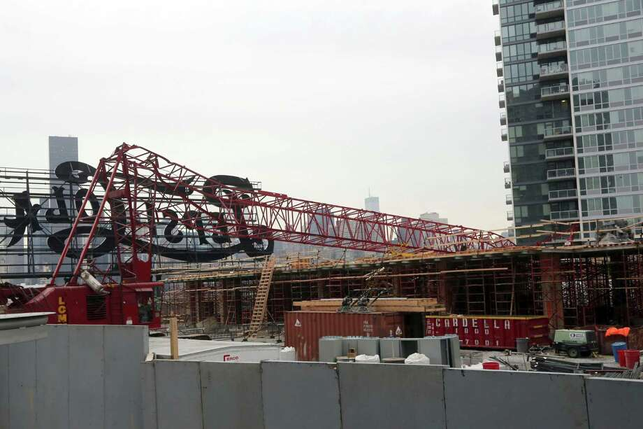 """A mangled crane lies at the construction site in the Queens borough of New York where it collapsed, Wednesday, Jan. 9, 2013, behind a big neon """"Pepsi Cola"""" sign, a local landmark. The Fire Department of New York says the 200-foot crane collapsed onto a building under construction, injuring seven people, three of them seriously. Photo: AP"""