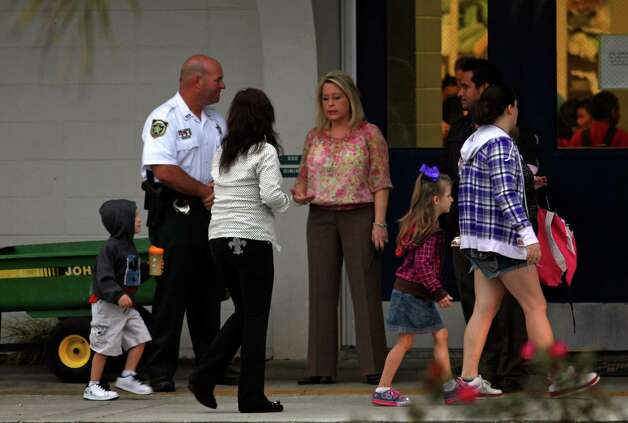 A Hillsborough County Sheriff's Deputy greet parents and children at Robinson Elementary School in Plant City, Fla., early Monday. Both Tampa Police and the Hillsborough County Sheriff's Office will keep a police presence in elementary schools in the wake of the Sandy Hook Elementary School shootings. (AP Photo/The Tampa Bay Times, Skip O'Rourke)  Photo: AP