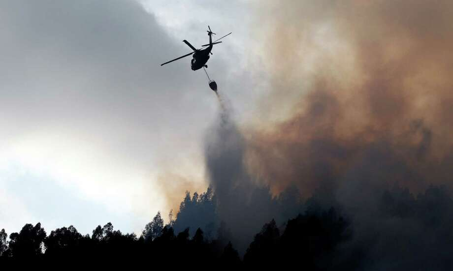 A firefighting helicopter drops water on a wildfire in a forest region of Cota, near  Bogota, Colombia, on Friday.  More than 34 acres of pine and eucalyptus trees on the outskirts of Bogota were destroyed by wildfires believed to have been sparked by a heat wave, authorities said. Photo: AP