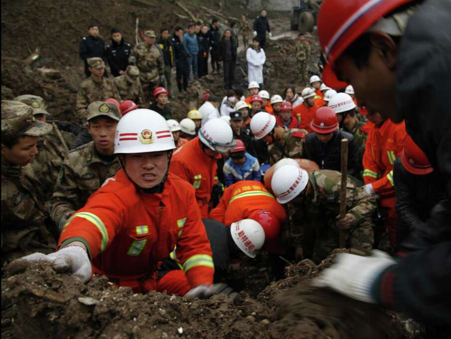 Rescuers work at the mud-inundated debris after a landslide hit Zhaojiagou in Zhenxiong County, southwest China's Yunnan Province on Friday. A landslide swept through the village in the steep, snow-dusted mountains of southern China on Friday, killing at least 32 people, the local government said.  (AP Photo/Xinhua Zhang Guangyu) Photo: AP
