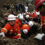 Rescuers work at the mud-inundated debris after a landslide hit Zhaojiagou in Zhenxiong County, southwest China's Yunnan Province on Friday. A landslide swept through the village in the steep, snow-dusted mountains of southern China on Friday, killing at least 32 people, the local government said.  (AP Photo/Xinhua Zhang Guangyu)