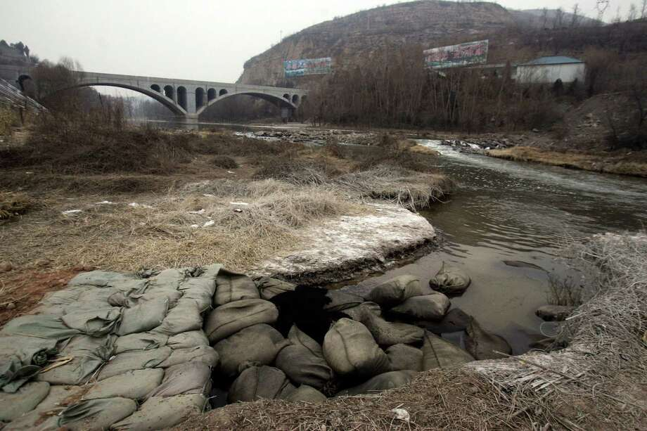 Bags of charcoal are placed in the Zhuozhang river on Jan. 6 to absorb aniline after a chemical plant leaked about 9 tons of it into the river in northern China's Shanxi province. A Chinese city government has apologized for taking five days to report the chemical leak that has affected another city's drinking water supply.  Photo: AP