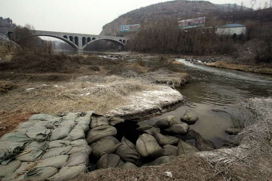 Bags of charcoal are placed in the Zhuozhang river on Jan. 6 to absorb aniline after a chemical plan