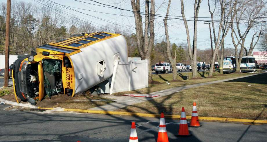 An overturned school bus rests on a fence after colliding with a commuter bus, back right on Thursday in Old Bridge, N.J. The New York City-bound commuter bus and the mini school bus crashed on a state highway in New Jersey, injuring at least 17 people, two critically.  School officials said no students were on the Old Bridge school bus, which landed on its side along Route 9. Photo: AP
