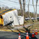 An overturned school bus rests on a fence after colliding with a commuter bus, back right on Thursday in Old Bridge, N.J. The New York City-bound commuter bus and the mini school bus crashed on a state highway in New Jersey, injuring at least 17 people, two critically.  School officials said no students were on the Old Bridge school bus, which landed on its side along Route 9.