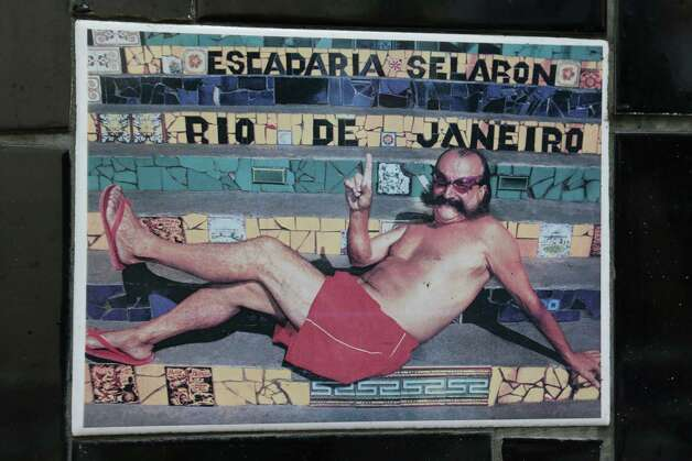 "An undated photo of Chilean artist Jorge Selaron decorates a tile that is part of a wall on a public staircase he decorated and titled the ""Selaron Stairway"" in Rio de Janeiro, Brazil, on Thursday. Selaron, an eccentric Chilean artist and longtime Rio resident who created a massive, colorful tile stairway in the bohemian Lapa district that's popular with tourists, was found dead on the stairway on Thursday. Authorities said he may have taken his own life by setting himself on fire on the very steps of his masterpiece. Photo: AP"