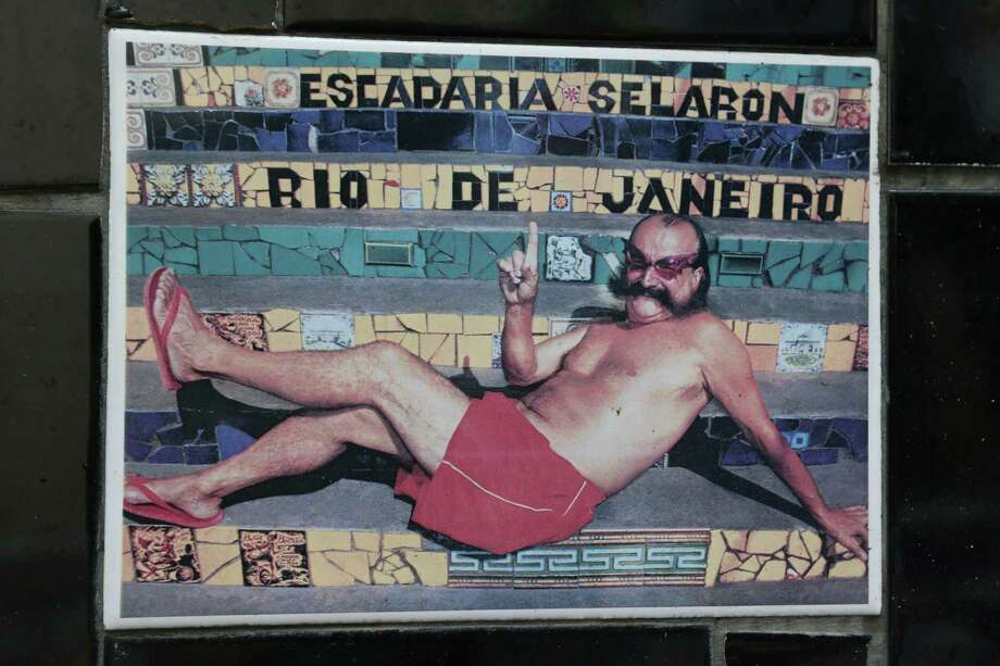 """An undated photo of Chilean artist Jorge Selaron decorates a tile that is part of a wall on a public staircase he decorated and titled the """"Selaron Stairway"""" in Rio de Janeiro, Brazil, on Thursday. Selaron, an eccentric Chilean artist and longtime Rio resident who created a massive, colorful tile stairway in the bohemian Lapa district that's popular with tourists, was found dead on the stairway on Thursday. Authorities said he may have taken his own life by setting himself on fire on the very steps of his masterpiece. Photo: AP"""