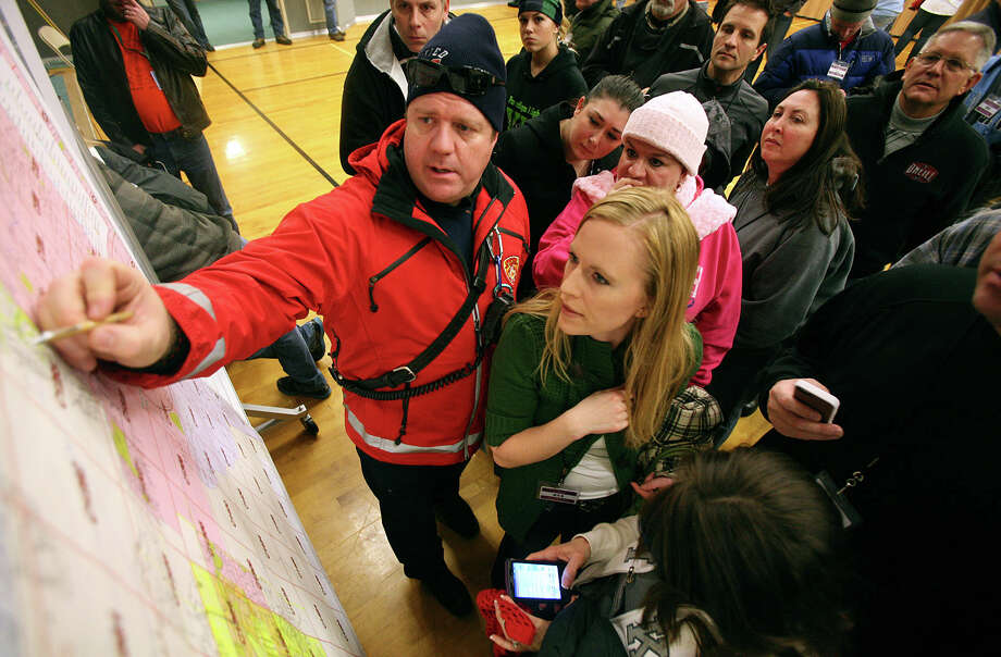 Unified firefighter Chris Thurman points out a meeting point to Christi Green and other volunteers before they leave to help search for 13-year-old Brooklyn Gittins a  in Herriman, Utah, on Thursday.  Several hundred volunteers dressed for the cold showed up at a Mormon meetinghouse Thursday to help search for a 13-year-old Utah girl who went missing without her shoes, coat or cellphone. Police say the girls was found unharmed and they were looking for her possible captors. (AP Photo/Kristin Murphy, Deseret News)  Photo: AP