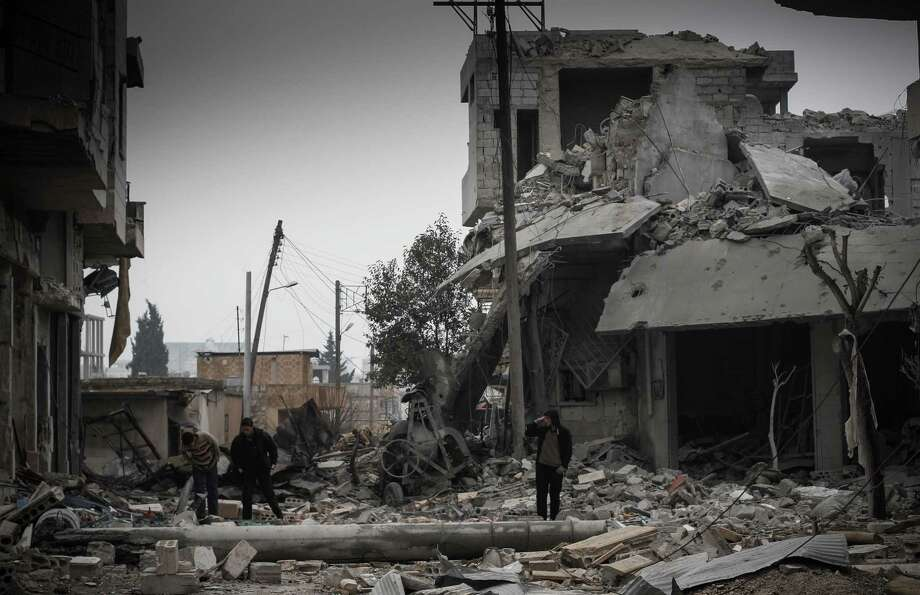"""Syrians inspect the destruction of buildings after heavy shelling on Jan. 5 by the Syrian Air Force in apparent retaliation for  rebels attacks on the nearby Taftanaz military airbase in the village of Binnish, Syria. Syrian President Bashar Assad, in a rare speech Sunday, outlined his own vision for ending the country's conflict with a plan that would keep him in power. He also dismissed any chance of dialogue with the armed opposition and called on Syrians to fight what he called """"murderous criminals."""" Photo: AP"""