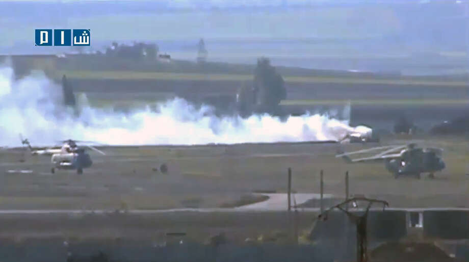 In this photo taken from video obtained from the Shaam News Network, which has been authenticated based on its contents and other AP reporting, rebel fighters battle on Thursday for control of the military airport  in Taftanaz, Idlib province, northern Syria. Syrian rebels and Islamic militants seeking to topple President Bashar Assad took full control of the Taftanaz air base on Friday in a significant blow to government forces, seizing helicopters, tanks and multiple rocket launchers, activists said. Photo: AP