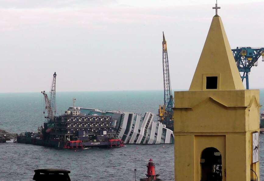 The cruise ship Costa Concordia, leaning on its side, is framed by a church bell tower in the Tuscan