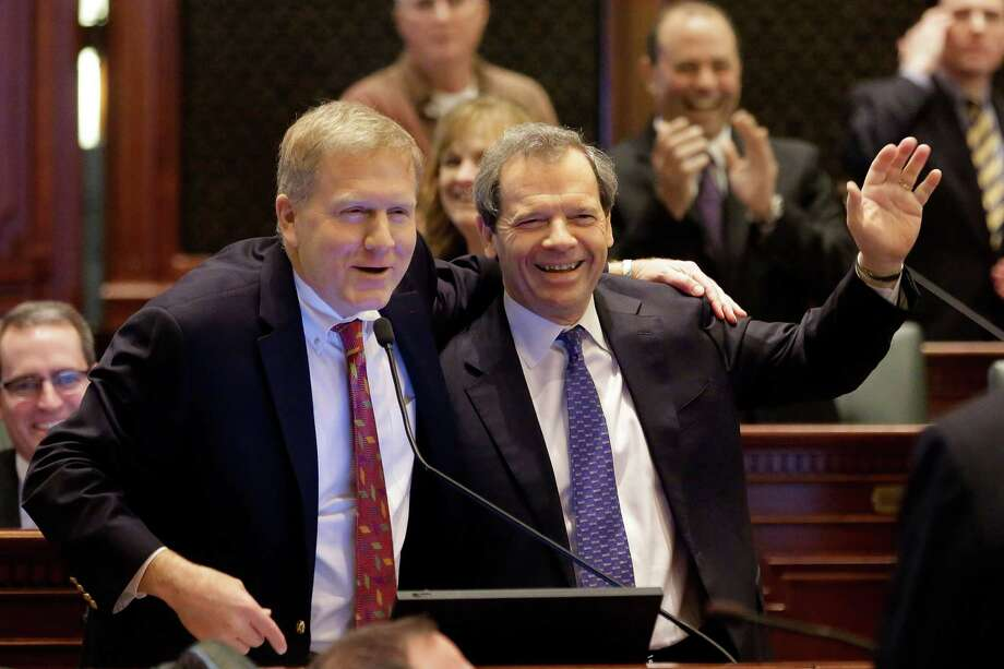 Illinois House Minority Leader Tom Cross, R-Oswego, left, welcomes Illinois Senate President John Cullerton, D-Chicago, right, to the House floor during session at the Illinois State Capitol on Tuesday in Springfield Ill. The long-awaited plan to address Illinois' $96 billion pension problem cleared an early hurdle Monday, as the Illinois House committee approved a proposal that freezes cost-of-living increases and calls for higher employee contributions. Photo: AP