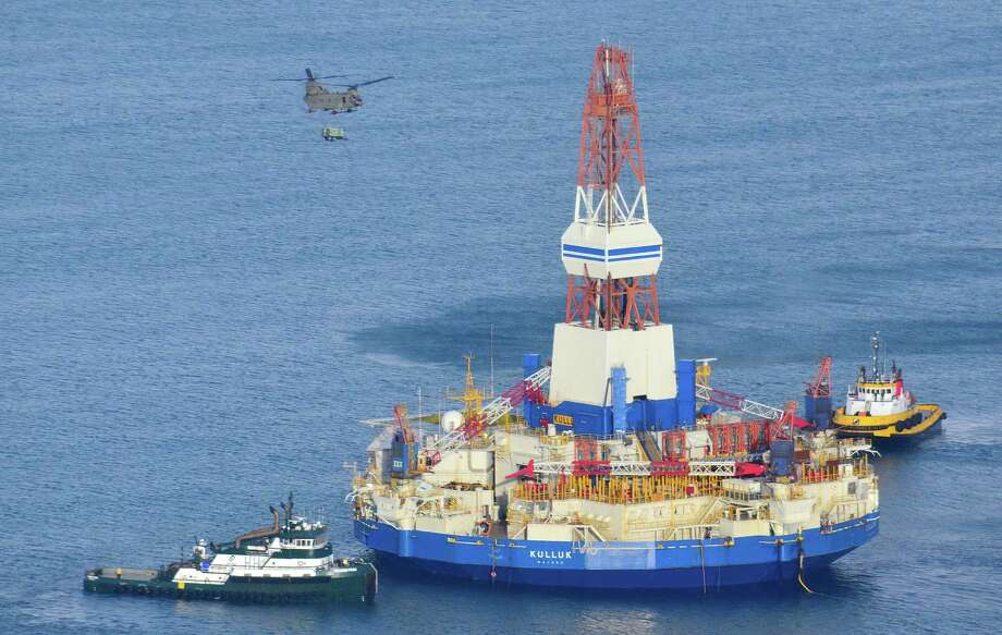 This aerial photo shows a U.S. Army CH-47 Chinook helicopter sling a trailer aboard the Shell floating drill rig in Kodiak Island, Alaska's Kiliuda Bay on Monday afternoon as salvage teams conduct an in-depth assessment of its seaworthiness. The Kulluk, which ran aground a week ago on Sitkalidak Island near Kodiak, was taken to Kiliuda Bay for repairs and a survey. Photo: AP