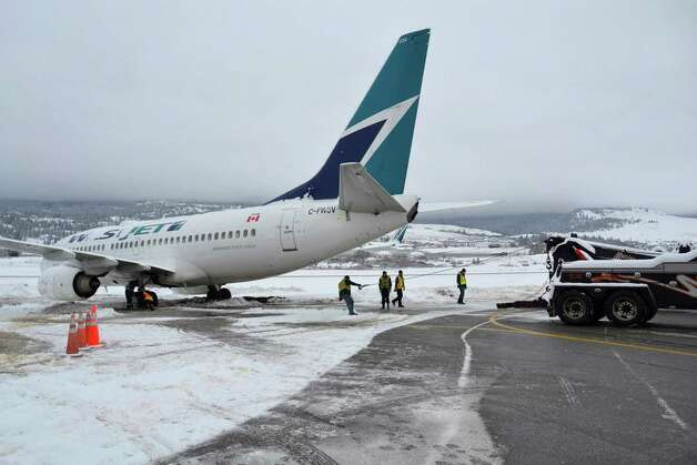 A WestJet Boeing 737-700 aircraft ended up in the mud off an apron next to the Kelowna International Airport terminal Monday. Two large tandem tow trucks attached cables to its rear wheels and slowly pulled it back onto the pavement. The 138 passengers and six crew disembarked with passengers booked on other flights or given hotel vouchers. Photo: AP