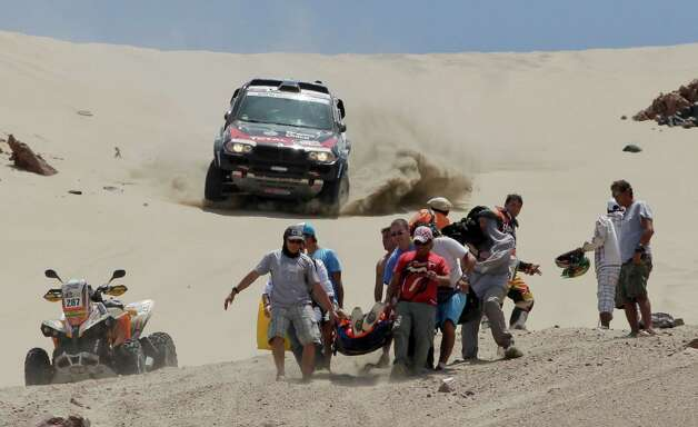 Orlando Terranova of Argentina and co-driver Paulo Fiuza of Portugal drive their BMW, top, as medics evacuate Leonardo Martinez of Bolivia after crashing with his quad in the 3nd stage of the 2013 Dakar Rally from Pisco to Nazca, Peru, on Monday. The race finishes in Santiago, Chile, on Jan. 20. Photo: AP