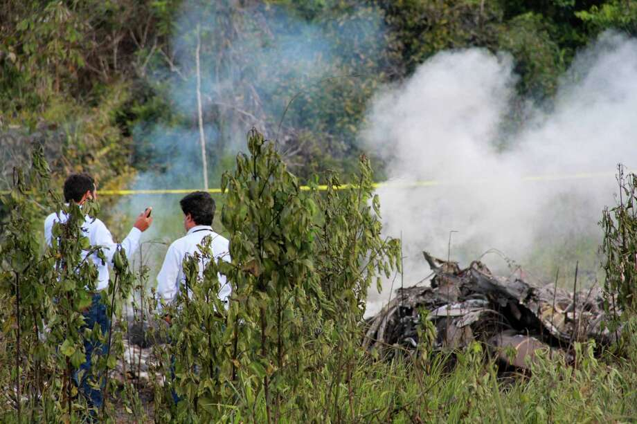 Investigators stand near the wreckage of a U.S.-owned cargo helicopter in Pucallpa, Peru, on Monday. Five U.S. citizens are among seven people killed in the crash in the Peruvian jungle. The heavy-lift, twin-rotor Chinook BH-234 chopper, owned by Columbia Helicopters in the Portland suburb of Aurora, Oregon, crashed Monday shortly after taking off from the provincial capital of Pucallpa bound for Tarapoto. Photo: AP