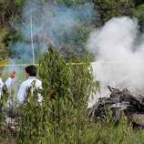 Investigators stand near the wreckage of a U.S.-owned cargo helicopter in Pucallpa, Peru, on Monday. Five U.S. citizens are among seven people killed in the crash in the Peruvian jungle. The heavy-lift, twin-rotor Chinook BH-234 chopper, owned by Columbia Helicopters in the Portland suburb of Aurora, Oregon, crashed Monday shortly after taking off from the provincial capital of Pucallpa bound for Tarapoto.