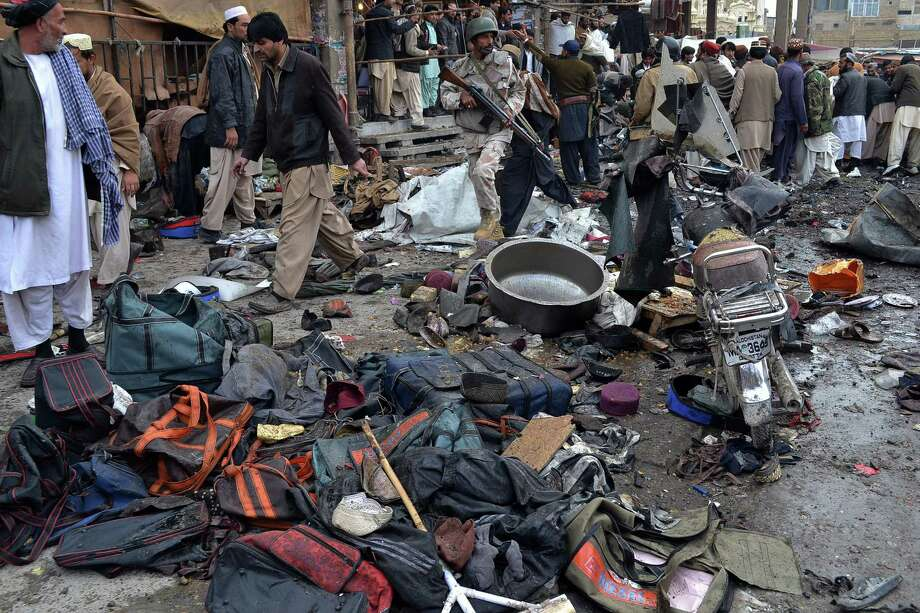 A Pakistani paramilitary soldier and local residents gather at the site of a bomb blast that targeted paramilitary soldiers in a commercial area in Quetta, Pakistan, killing at least 12 people and wounding more than 40 others, according to police on Thursday. A series of bombings in different parts of Pakistan killed 115 people on Thursday in one of the deadliest days in the country in recent years. Photo: AP