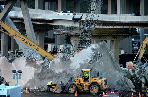 Workers clean up debris from a fallen piece of the old SR 16 at South Tacoma Way late Friday afternoon. A Washington state Transportation Department spokeswoman says a section of a concrete pillar fell during demolition of the old highway overpass, punching a hole in a water line. Photo: AP