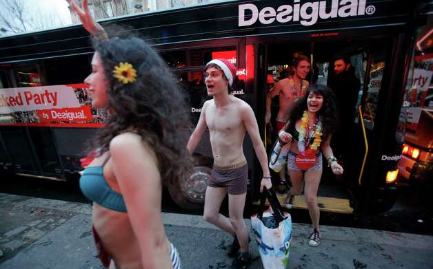 Semi-naked shoppers get out a bus for the opening of a Spanish fashion store to mark winter sales in Paris on Wednesday. The brand offers free clothes for the first hundred semi-naked customers. Photo: AP