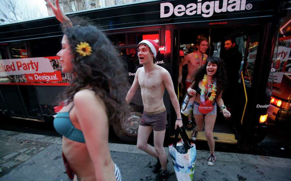 Semi-naked shoppers get out a bus for the opening of a Spanish fashion store to mark winter sales in