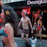 Semi-naked shoppers get out a bus for the opening of a Spanish fashion store to mark winter sales in Paris on Wednesday. The brand offers free clothes for the first hundred semi-naked customers.
