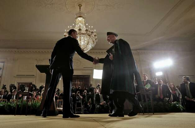 President Barack Obama shakes hands with Afghan President Hamid Karzai at the conclusion of their joint news conference in the East Room of the White House in Washington on Friday. The two said most U.S. combat operations in Afghanistan would end 