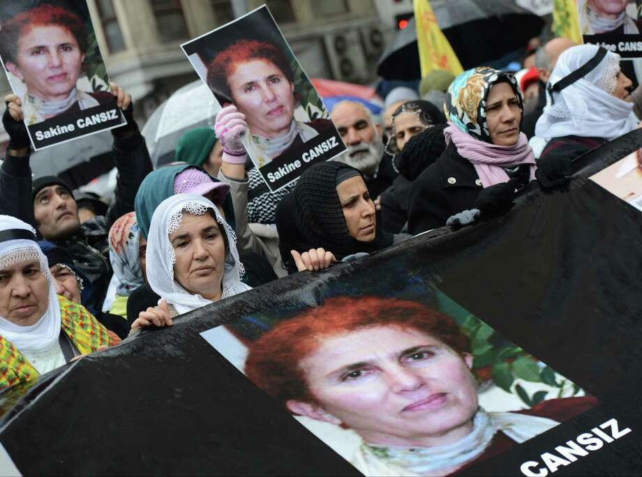 "Kurds hold photos of Sakine Cansiz, one of the founders of a militant group battling Turkish troops since 1984, as they protest against France outside the French consulate in Istanbul, Turkey, on Friday. Cansiz and two other women were ""executed"" at a Kurdish center in Paris, Thursday. It was not immediately clear who killed the women, who belonged to the PKK, a group that Turkey and its Western allies, including the United States and the European Union, consider a terrorist organization. Photo: AP"