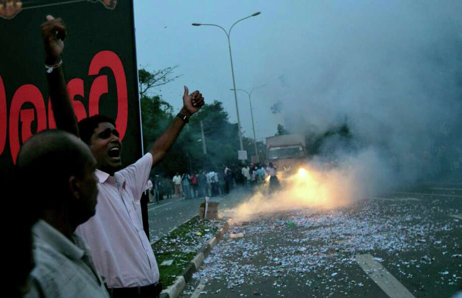 Supporters of Sri Lanka's president Mahinda Rajapaksa light firecrackers to celebrate upon hearing the result of the vote to  impeach the country's Chief Justice Shirani Bandaranayake in Colombo, Sri Lanka, on Friday. Sri Lanka's Parliament voted overwhelmingly on Friday to impeach the chief justice, deepening a standoff between the judiciary and the government, which is controlled by the country's most powerful family. Photo: AP