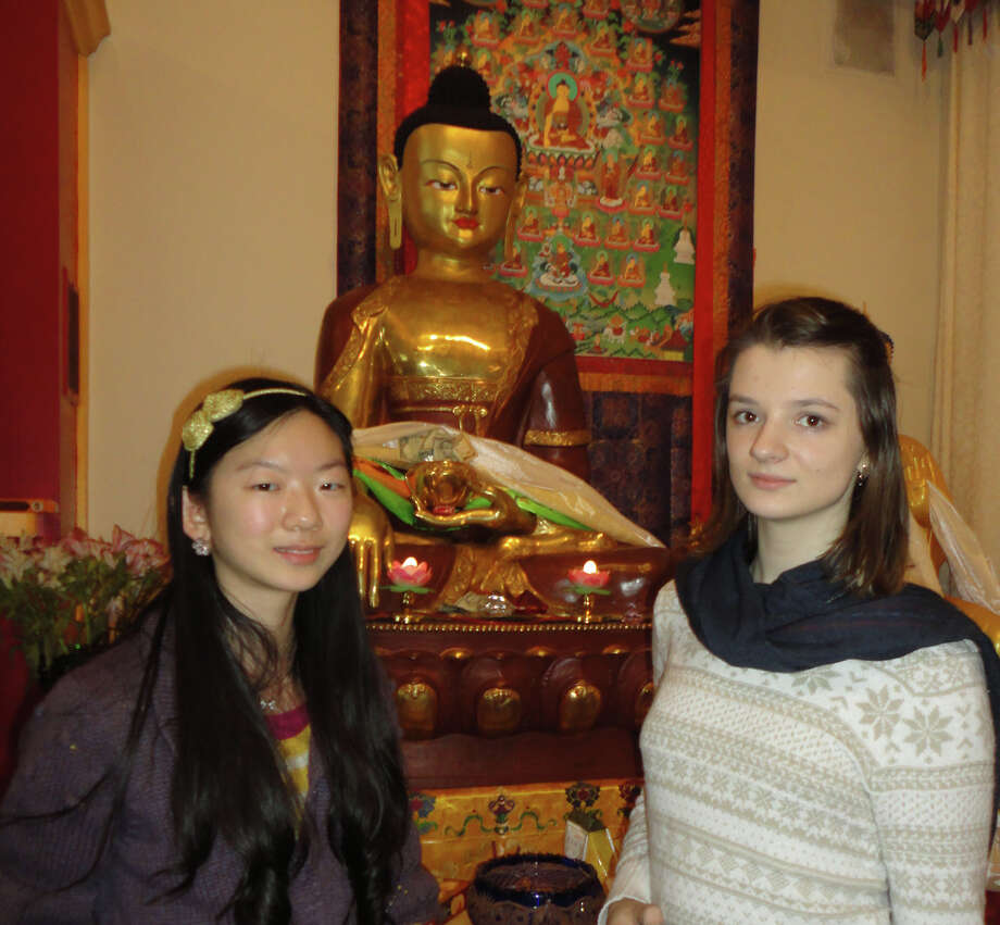 Chiana Yang, left, 14, and Alisa Korneyeva, 15, freshmen at Fairfield Warde High School, in front of a statue of Buddha at the Tibetan Buddhist Center for Universal Peace in Redding, which they visited Tuesday.  Fairfield CT 1/8/13 Photo: Meg Barone / Fairfield Citizen freelance