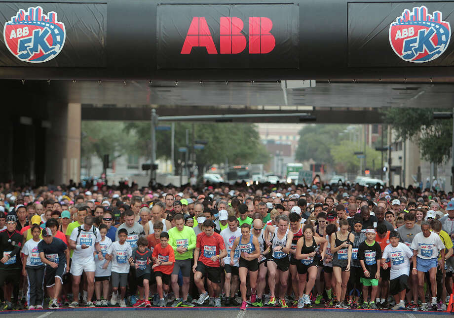 Runners open Saturday's ABB 5K ahead of Sunday's Chevron Houston Marathon. The runners are given a time limit of 90 minutes to complete the race of about three miles. Photo: James Nielsen / © Houston Chronicle 2013