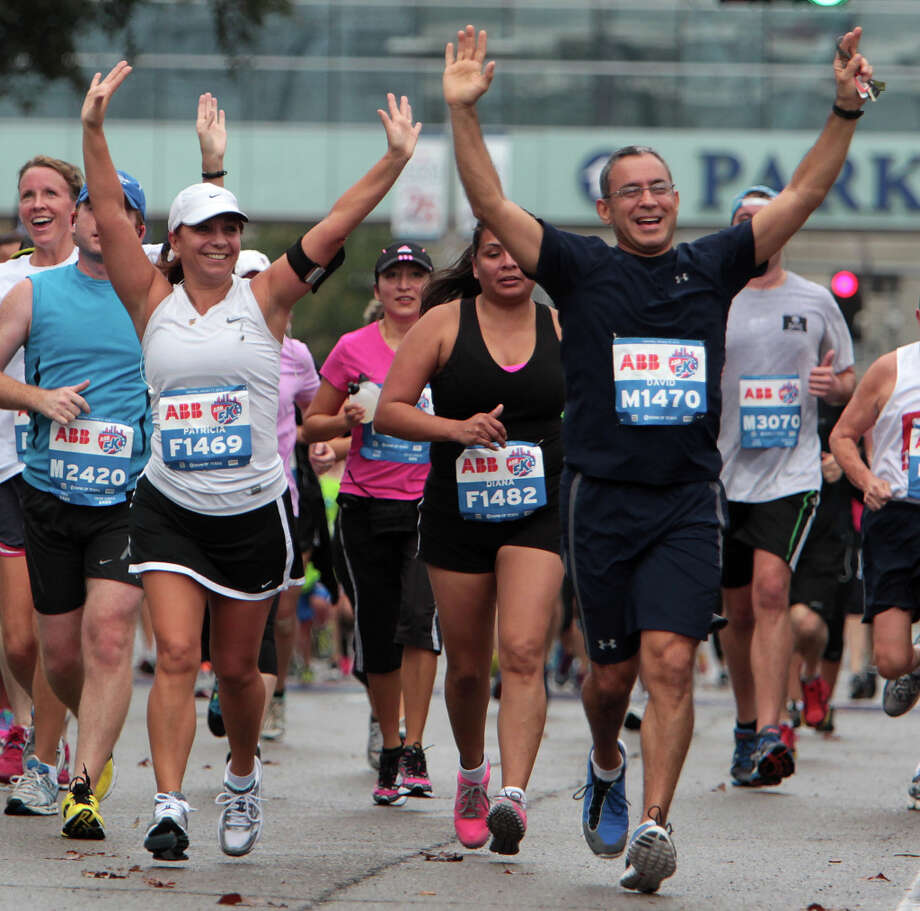Patricia Donatti and David Salinas raise their arms in the air as they near the finish line of the ABB 5K race. Photo: James Nielsen / © Houston Chronicle 2013