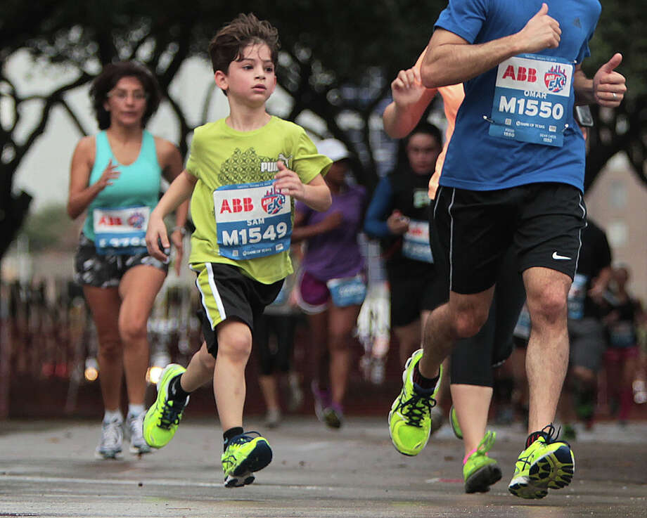 Seven-year-old Sam Saman center, nears the finish line of the ABB 5K race. Photo: James Nielsen / © Houston Chronicle 2013