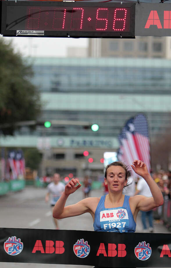 Annika Braun crosses the finish line to win the women's division of the ABB 5K race with an official time of 17:57. Photo: James Nielsen / © Houston Chronicle 2013