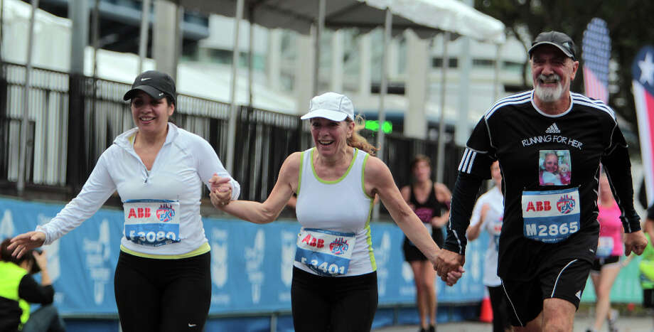 Carolina Cutrera left, Monica Cutrera center, and Roberton Cutrera right run hand in hand as they near the finish line of the ABB 5K race. Photo: James Nielsen / © Houston Chronicle 2013
