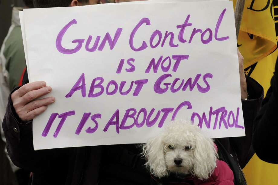 Joan Korman of Niskayuna and her Toy Poodle Roberre take pat in a pro gun rights rally outside the Saratoga Springs City Center during the Saratoga Springs gun show on Saturday Jan. 12,2013 in Saratoga Springs, N.Y. (Michael P. Farrell/Times Union) Photo: Michael P. Farrell