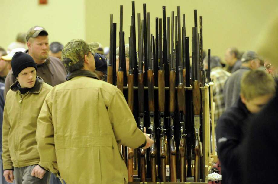 Firearm enthusiast look over the offerings at the Saratoga Springs gun show on Saturday Jan. 12,2013 in Saratoga Springs, N.Y. (Michael P. Farrell/Times Union) Photo: Michael P. Farrell
