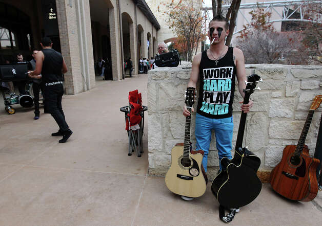 Alex Robertson, 24, from Houston smokes a cigarette and holds on to guitars while waiting to audition for the show, America's Got Talent, at the Henry B. Gonzales Convention Center on Saturday, Jan. 12, 2013. Numerous people stood in a line that wrapped around the convention center for a chance to show their talents and skills and for a chance to win $1 million. Robertson is part of the band called Soul In Tension. Photo: Kin Man Hui, San Antonio Express-News / © 2012 San Antonio Express-News