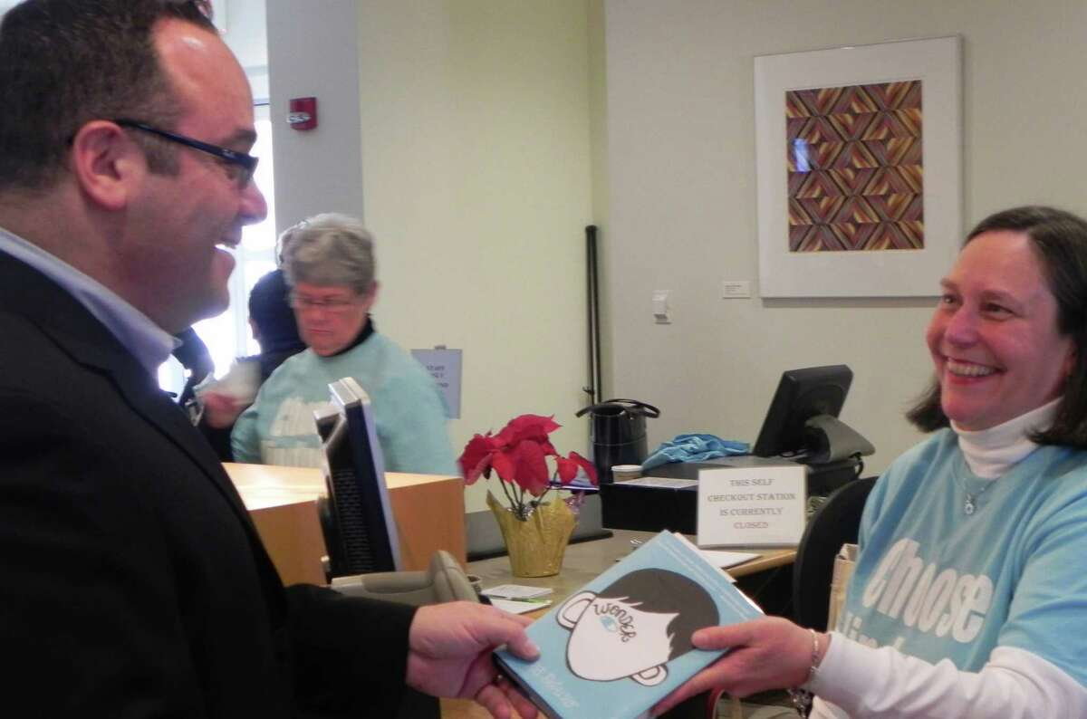 """Bob Sussman, treasurer of the Fairfield Public Library Boards of Trustees and owner of Fairfield Center Jewelers, was one of the first Thursday to check out the book, """"Wonder,"""" from Anne Farkas of the circulation staff. FAIRFIELD CITIZEN, CT 1/10/13"""