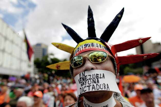 "An opponent of Venezuela's President Hugo Chavez wears a message over his mouth that reads in Spanish, ""In Venezuela there is a dictatorship,"" during an outdoor gathering in Caracas, Venezuela, Saturday, Jan. 12, 2013. Venezuelan opposition politicians say they're preparing to present a case before a regional human rights court to challenge a Supreme Court decision that permits the indefinite postponement of President Hugo Chavez's inauguration. (AP Photo/Ariana Cubillos) Photo: Ariana Cubillos"