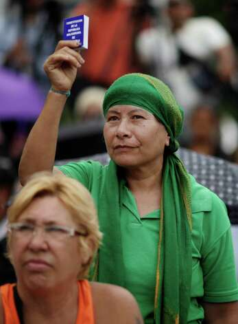 An opponent of Venezuela's President Hugo Chavez holds up a miniature copy of Venezuela's constitution during an outdoor gathering in Caracas, Venezuela, Saturday, Jan. 12, 2013. Venezuelan opposition politicians say they're preparing to present a case before a regional human rights court to challenge a Supreme Court decision that permits the indefinite postponement of  the ailing president's inauguration. (AP Photo/Ariana Cubillos) Photo: Ariana Cubillos