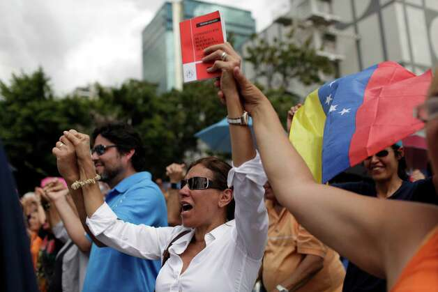 Opponents of Venezuela's President Hugo Chavez chant during an outdoor gathering in Caracas, Venezuela, Saturday, Jan. 12, 2013. Venezuelan opposition politicians say they're preparing to present a case before a regional human rights court to challenge a Supreme Court decision that permits the indefinite postponement of President Hugo Chavez's inauguration. (AP Photo/Ariana Cubillos) Photo: Ariana Cubillos