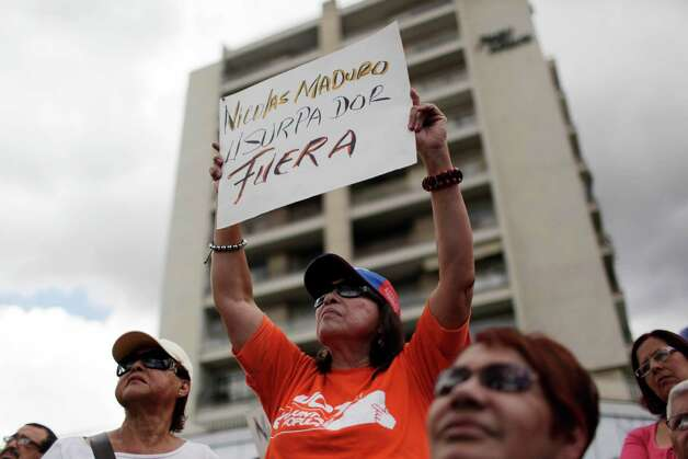 "An opponent of Venezuela's President Hugo Chavez holds up a sign that reads in Spanish, ""Maduro is an usurper,"" during an outdoor gathering in Caracas, Venezuela, Saturday, Jan. 12, 2013. Venezuelan opposition politicians say they're preparing to present a case before a regional human rights court to challenge a Supreme Court decision that permits the indefinite postponement of President Hugo Chavez's inauguration. (AP Photo/Ariana Cubillos) Photo: Ariana Cubillos"
