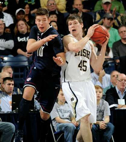 Notre Dame forward Jack Cooley, right, grabs a rebound away from Connecticut forward Tyler Olander during the first half of an NCAA college basketball game,  Saturday, Jan. 12, 2013, in South Bend, Ind. (AP Photo/Joe Raymond) Photo: Joe Raymond, ASSOCIATED PRESS / ASSOCIATED PRESS
