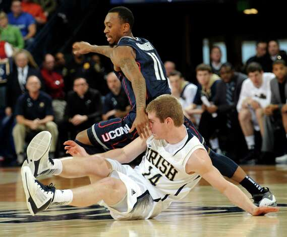 Connecticut guard Ryan Boatright, top, tangles up with Notre Dame guard Scott Martin during the second half of an NCAA college basketball game, Saturday, Jan. 12, 2013, in South Bend, Ind. Connecticut won 65-58. (AP Photo/Joe Raymond) Photo: Joe Raymond, ASSOCIATED PRESS / Associated Press